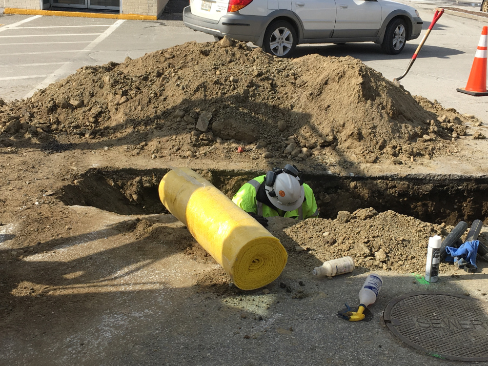 Summit Natural Gas pipeline inspector Joe Michaud works in a hole Thursday afternoon on repairs to a gas leak. Michaud said crews cut out a piece of the line that needed to be repaired.