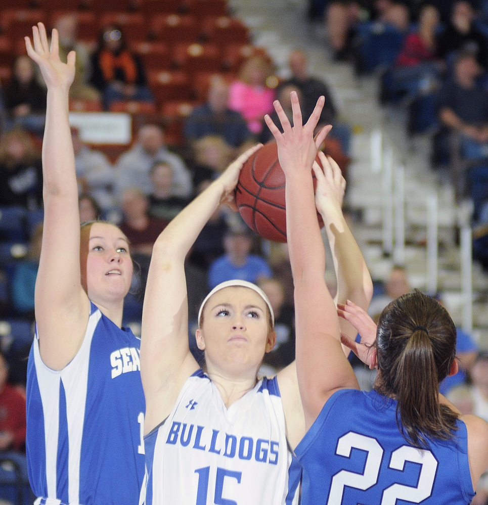 Madison Area Memorial High School's Lauren Hay grabs a rebound between Searsport District High School's Arianna Stemp, left, and Anna Bucklin during a Class C South semifinal game Thursday in Augusta.