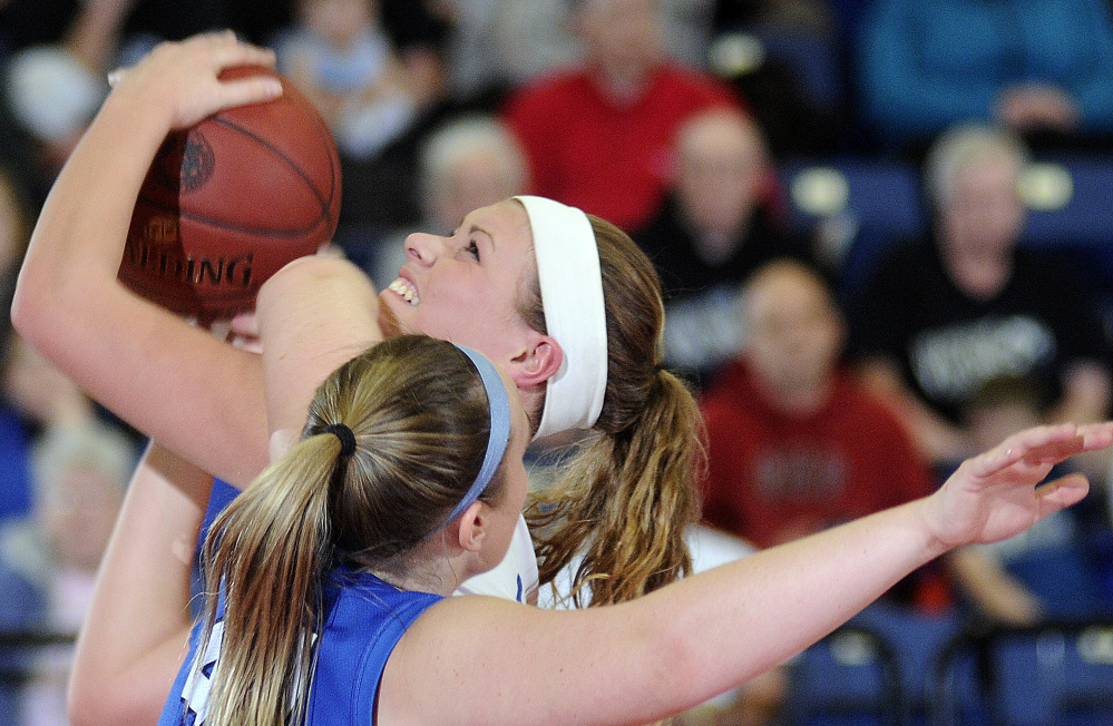 Madison Area Memorial High School's Erin Whalen gets a shot while being a fouled by Searsport District High School's Anna Bucklin during a Class C South semifinal game Thursday in Augusta.