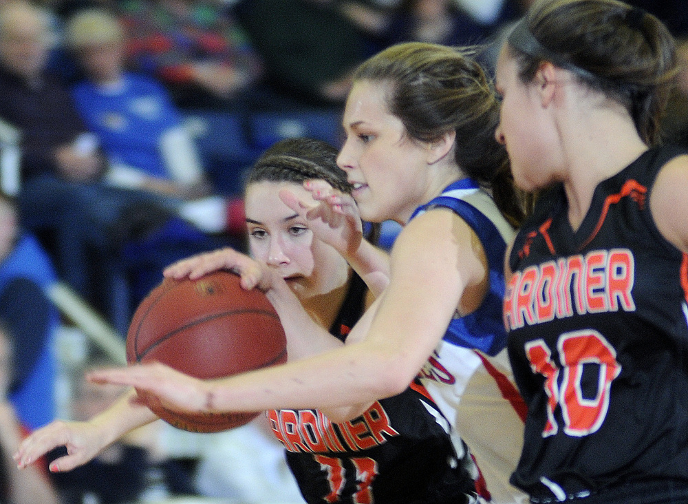 Gardiner's Leslie Stevens, left, and Leah Weymouth squeeze Messalonskee's Sophie Holmes, middle, during a Class A North girls semifinal Wednesday afternoon at the Augusta Civic Center.