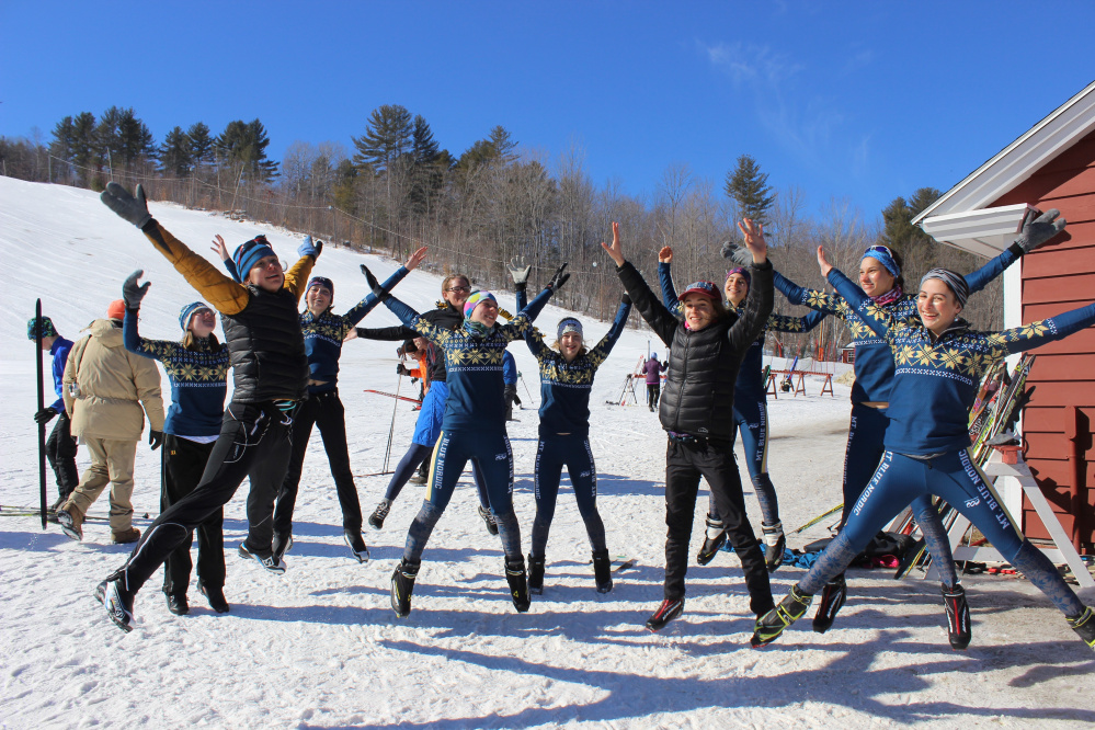 Mt. Blue coach Claire Polfus, assistant coach Patty Veayo and members of the Mt. Blue Nordic ski team celebrate their Class A state championship Friday at Titcomb Mountain.