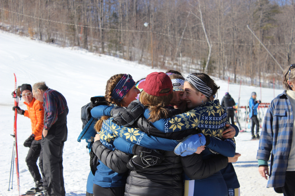 Mt. Blue Nordic skiers, from left, Zoe Huish (with braids), Julia Ramsey, Kayla White and River Lisius hug after the Cougars won the Class A Nordic state title Friday at Titcomb Mountain.