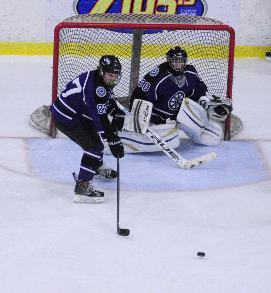 Waterville's sophomore defenseman Chase Wheeler stands in front of goalie Nathan Pinnette during a game against Lewiston earlier this season at the Androscoggin Bank Colisee.