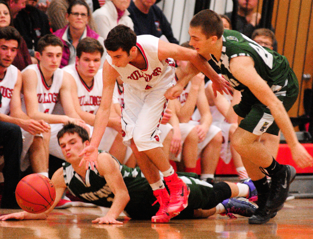 Winthrop juniors Bennett Brooks, left, and Andrew Pazdziorko, right, and Hall-Dale's Tyler Nadeau scramble for a loose ball in a game earlier this season at Penny Memorial Gym in Farmingdale. The junior class has played a big part in the Ramblers' run to the Class C South championship game.