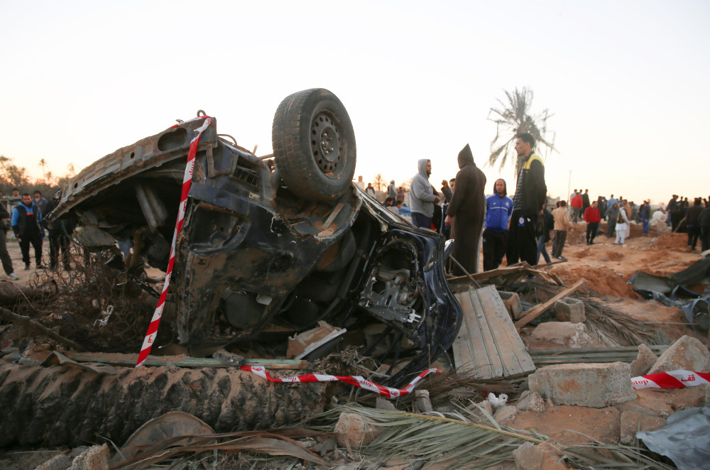 In this Friday photo, people gather by the wreckage of a car, after an air strike on a house and training camp belonging to the Islamic State group, west of Sabratha, Libya.