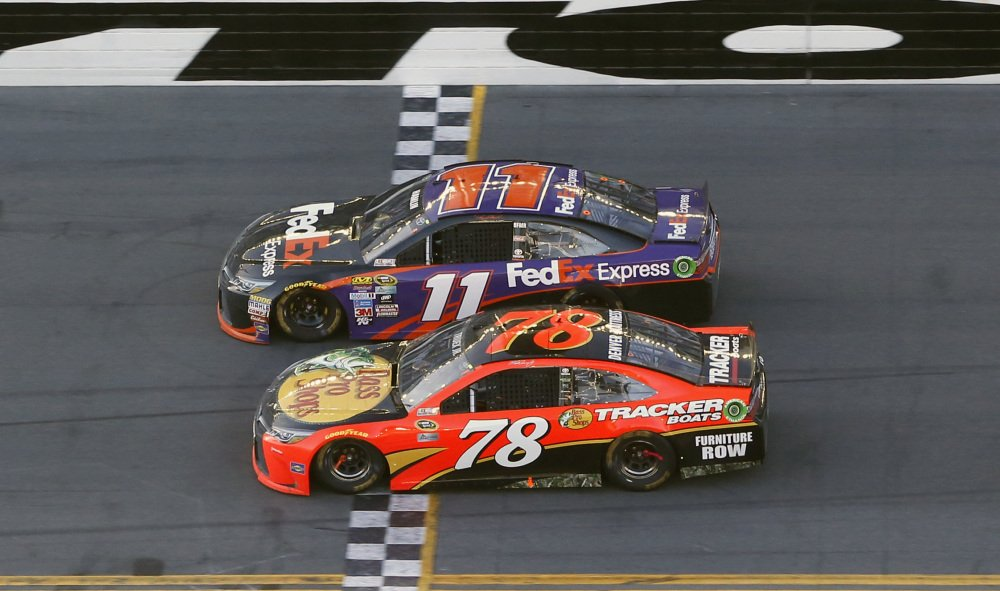 Denny Hamlin (11) beats out Martin Truex Jr. (78) at the finish line to win the Daytona 500 at Daytona International Speedway on Sunday in Daytona Beach, Florida.
