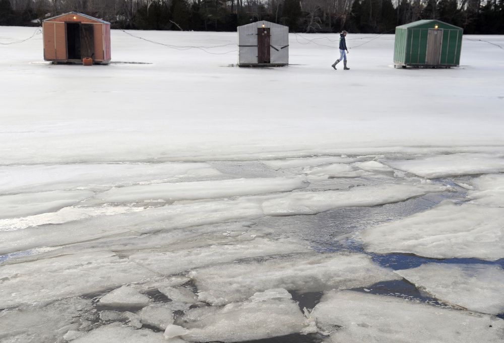 Peter James checks the smelt shacks Sunday on the Eastern River in Dresden his family maintains. Anglers have been successful fishing on the tides at James Eddy, he said, but the mild conditions and weak ice has curtailed the season.