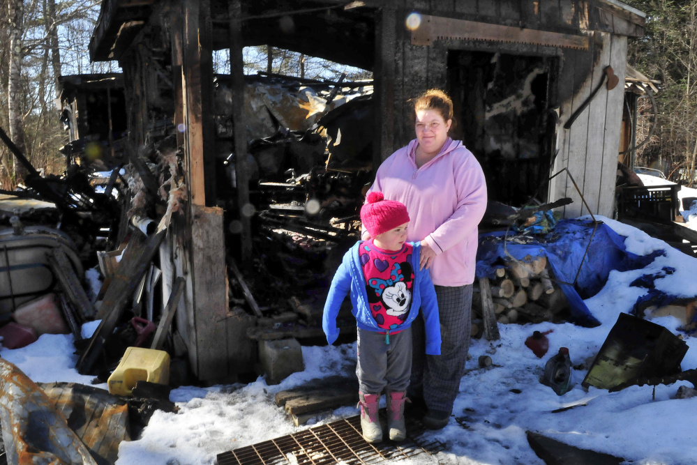 Tornia Bowring and her granddaughter, Serenity, on Monday, stand outside the Norridgewock home they and her husband Maurice lived in when it was destroyed by fire last month. The family and friends say someone has taken items donated by area stores for a March benefit for the family.