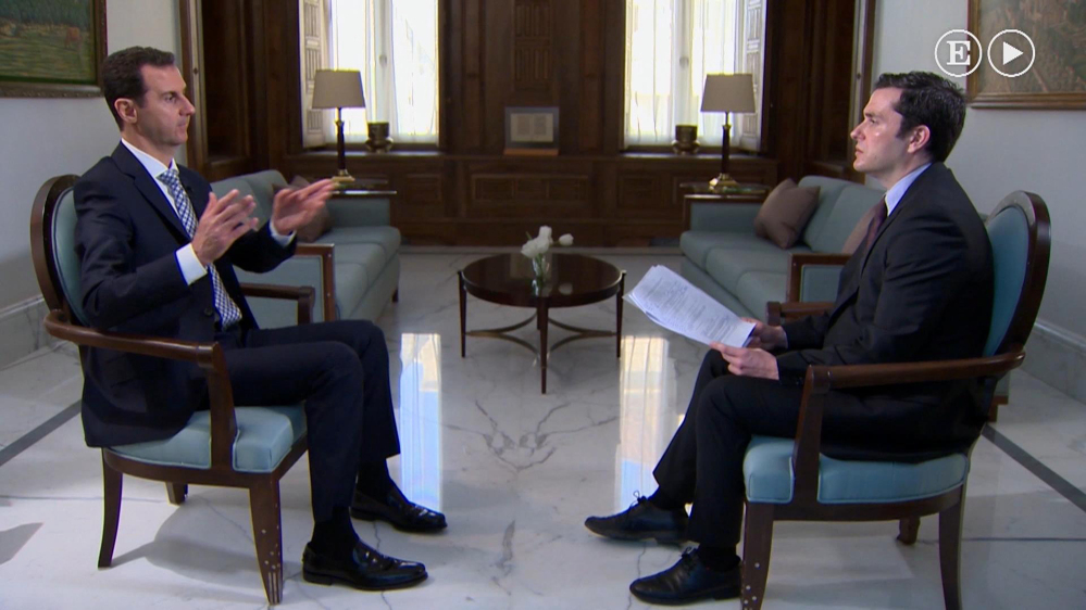 In this undated image made from video, Syrian President Bashar Assad, left, gestures while being interviewed in Damascus, Syria, by a journalist with Spanish El Pais newspaper published Sunday.