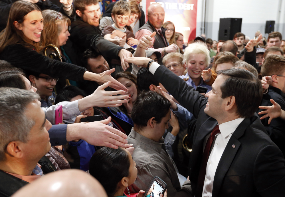 Republican presidential candidate, Sen. Marco Rubio, R-Fla., shakes hands with audience members during a campaign event, Tuesday in Kentwood, Mich.