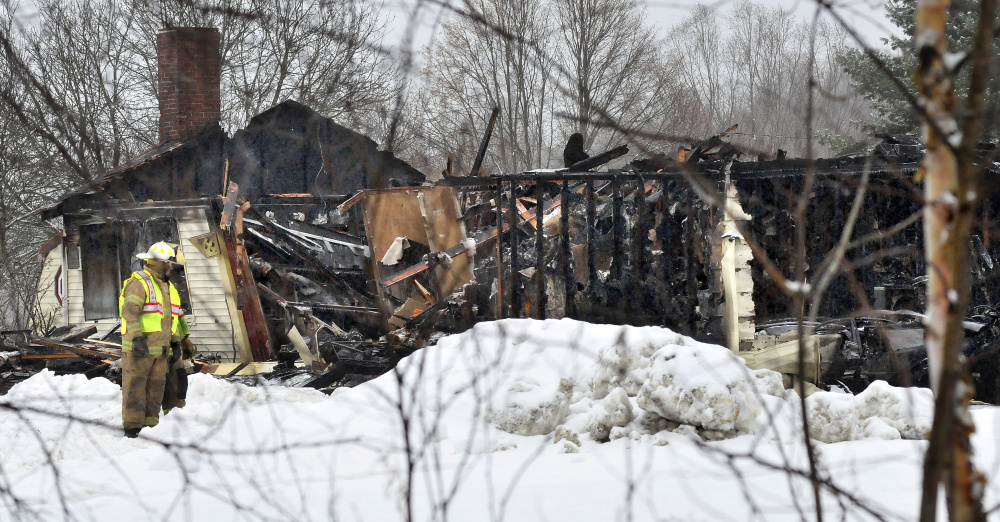 Firefighters outside the burned remains of a home on the Pease Hill Road in Anson on Wednesday. The fire is being investigated as a possible arson.