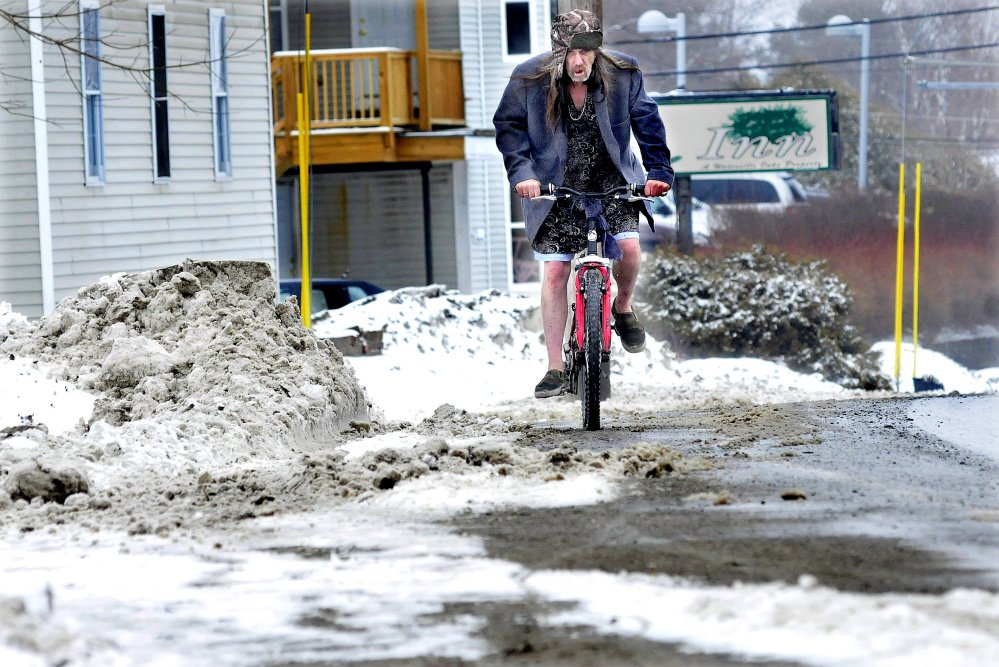 Wayne Norwood didn't let the snow, rain and slush stop him from riding his bike in shorts in Waterville on Wednesday. The warming temperatures turned the morning snow into a sloppy, wet mess.
