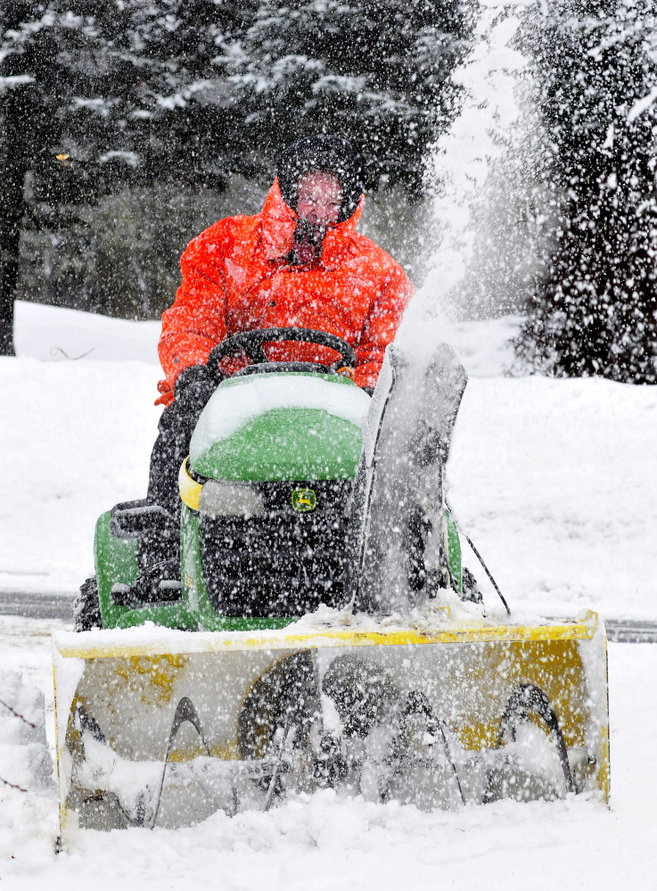 Earl Beaulieu got covered with the wet snow he was snowplowing at his home in Madison on Wednesday. The morning snowstorm changed to sleet then rain.