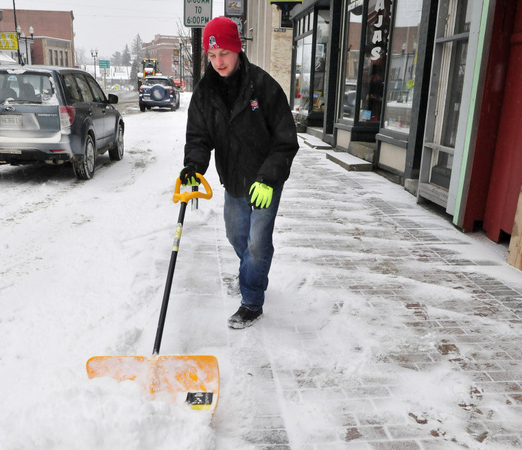 Chris Wacome shoveled snow from sidewalks in Skowhegan on Wednesday.
