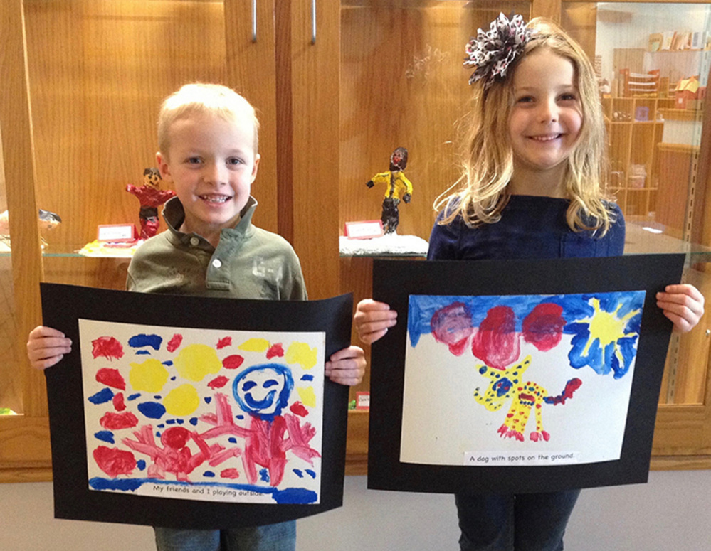 "Cape Cod Hill School kindergarten students Bailey Markham, left, and Emily Coffey display their ""sentence paintings with tempura."" The art will be part of a display at the Youth Art Month show at Upcountry Artists Gallery in Farmington."