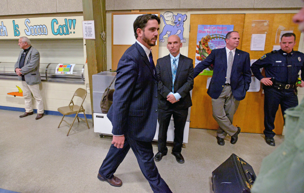Former Waterville Senior High School principal, Don Reiter, walks past Waterville police Detective Bill Bonney, left, and others after leaving a public hearing at George J. Mitchell School in Waterville in November. Reiter was dismissed from his position by the school board. Reiter's case is on hold while police investigate further, Kennebec County District Attorney Maeghan Maloney said Wednesday.