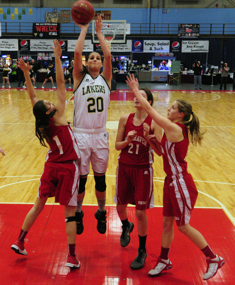 Rangeley's Blayke Morin shoots over a group of Vinalhaven defenders during the Class D South championship game on Saturday at the Augusta Civic Center.