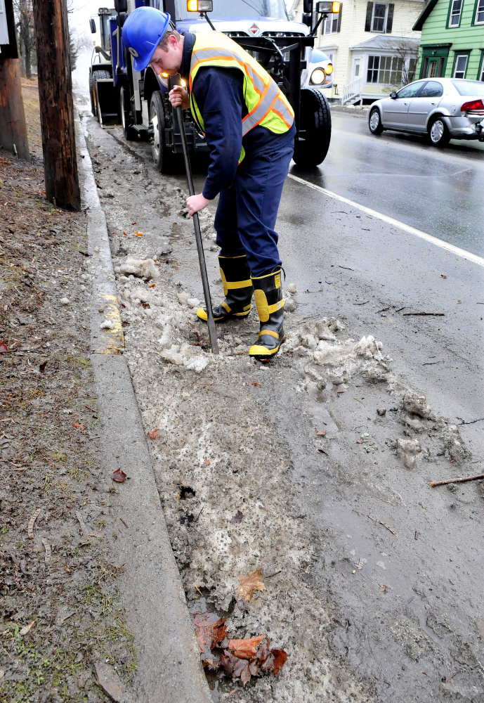 Josh Berryman of the Skowhegan Highway Department and other employees kept busy keeping drains open along roads left clogged with ice, slush and leaves from the heavy rains early Thursday.