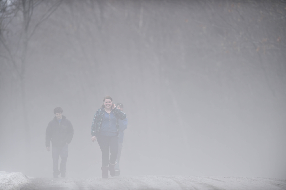 Ashlyn Laliberte, of Canaan, and Gilly Barrows, left, emerge from the fog as they walk along Quarry Road in Waterville on Thursday.