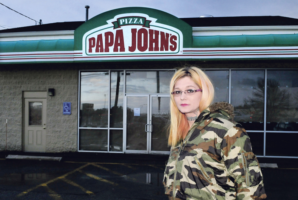 Papa John's restaurant manager Theresa Ratliff stands outside the closed business Thursday in Waterville.