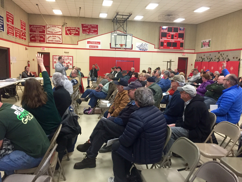 China residents raise their hands to ask questions during an informational meeting on a proposed pay-per-bag trash disposal program. Selectmen have agreed that rather than implementing a pilot program this summer, residents will vote on it in 2017 after strong opposition from residents.