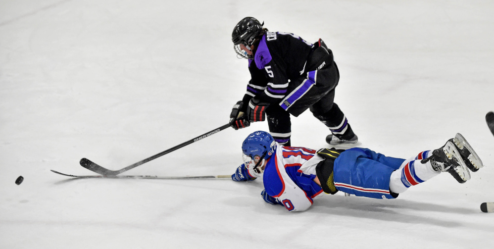 Messalonskee forward Brandon Nale (10) dives to the puck as John Bapst's Tyler Wheeler closes in during the third period of a Class B North quarterfinal Tuesday night at Sukee Arena.