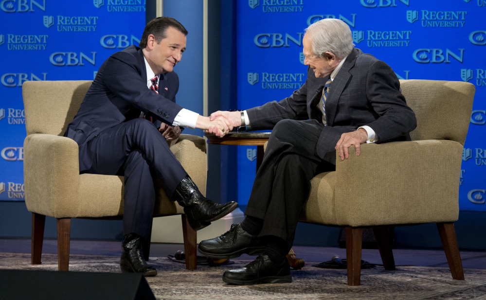 Republican presidential candidate, Sen. Ted Cruz, R-Tx., shakes hands with religious broadcaster Pat Robertson, right, during an appearance at Regent University in  Virginia Beach, Va., Friday.