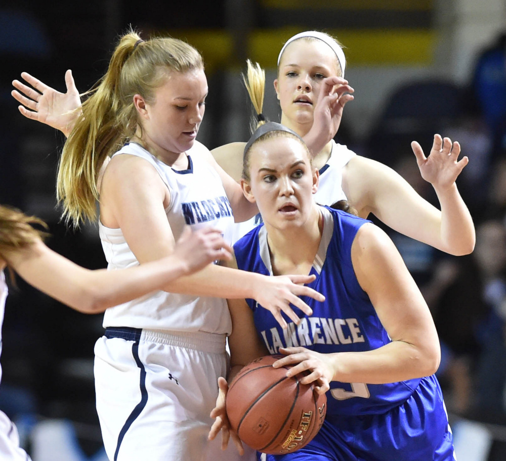 Lawrence senior center Nia Irving looks to pass as she is swarmed by York defenders during the Class A state championship game Saturday afternoon at the Cross Insurance Arena in Portland.
