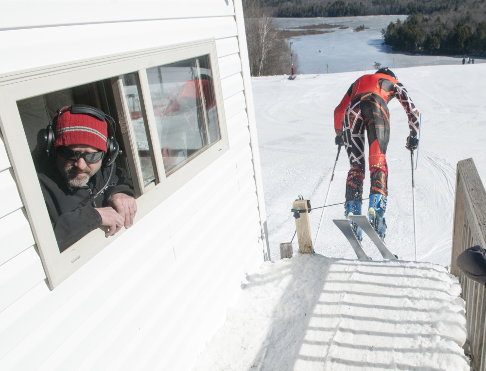 Starter John Rice, left, watches the next skier enter the start area as Maranacook student Robbie McKee, of Wayne, flies out of the starting gate Saturday during a slalom ski racing fundraiser and food drive at Kents Hill School in Readfield.