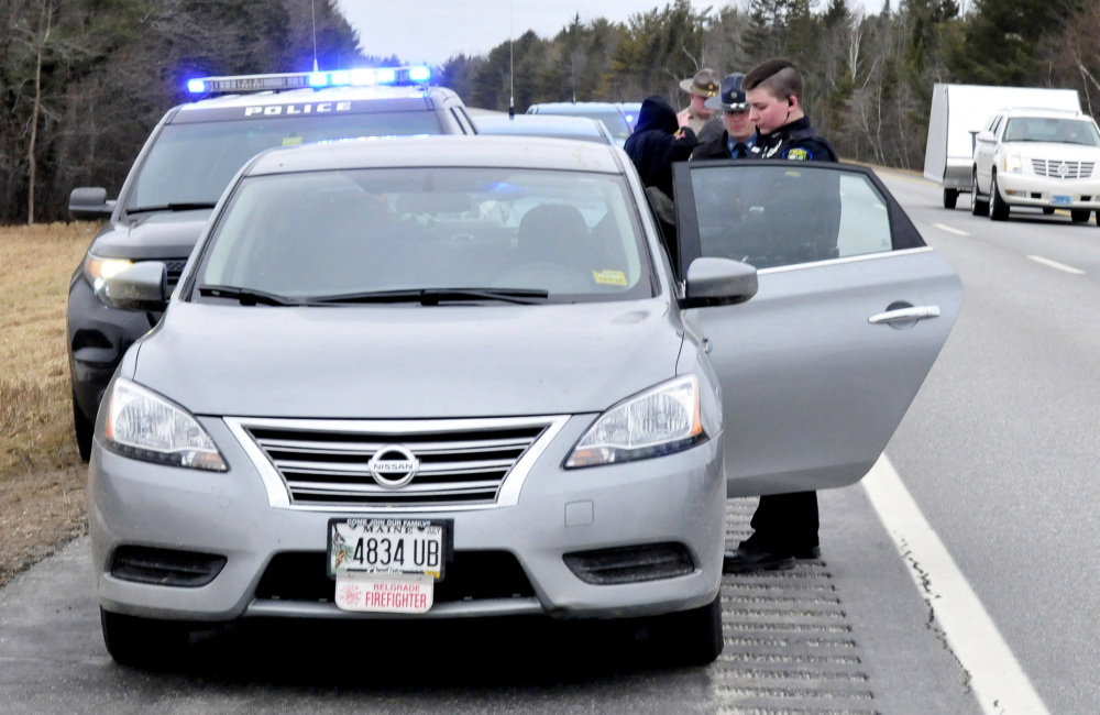 Skowhegan Police Officer Katelyn Treylino searches the contents of a car she pulled over on Interstate 95 in Newport following a chase that began in Skowhegan on Sunday. Maine State Police and a Somerset County sheriff's deputy interview the three juvenile occupants in background.