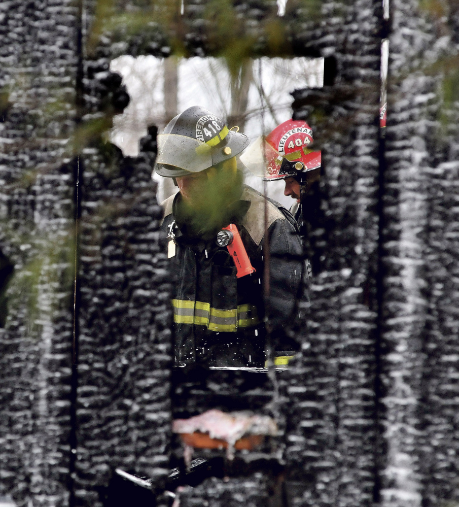 Firefighters can be seen through two burned out walls of a garage that was destroyed by fire on the Huff Hill Road in Hartland on Sunday.