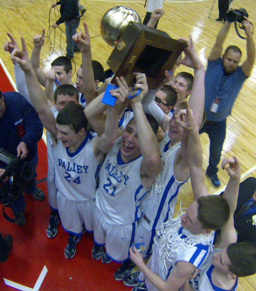 The Valley boys basketball team celebrates with the Gold Ball after it won the Class D state championship Saturday at Augusta Civic Center.
