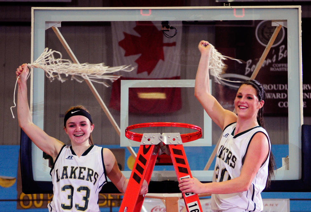 Rangeley's Maddison Egan, left, and Blayke Morin celebrate with freshly trimmed nets after the Lakers sank Shead in the Class D state championship game Saturday at Augusta Civic Center.