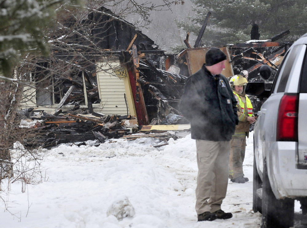Sgt. Ken Grimes, of the state fire marshal's office, speaks with another investigator outside a home that was destroyed by fire early Wednesday morning on Pease Hill Road in Anson. Investigators say the fire was set intentionally to cover up a break-in at the property.