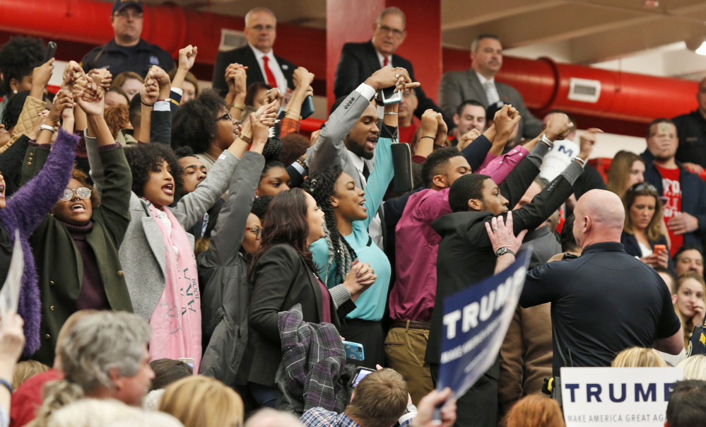 Protesters yell as they are escorted out of a rally for Republican presidential candidate, Donald Trump at Radford University in Radford, Va., Monday.
