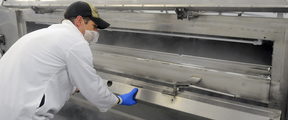Butcher Moe Howard examines the interior of the flash freezer tunnel Monday at Central Maine Meats in Gardiner.
