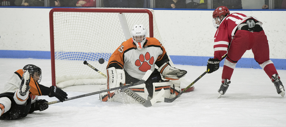 Gardiner goalie Michael Poirier gets in position to stop a shot by Cony forward Riley Boivin during a game at the Ice Vault earlier this season.