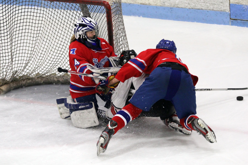 Messalonskee freshman goalie Amber Kochaver holds her ground as teammate Dylan Burton falls on a Camden Hills player in front of the net during a Class B North semifinal Saturday at Sukee Arena.