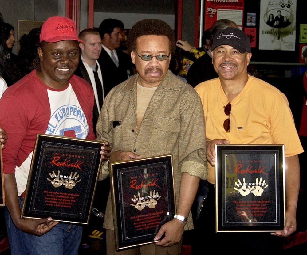 Philip Bailey, left, Maurice White, center, and Ralph Johnson of Earth Wind & Fire hold up the plaques from their induction to the Hollywood Rock Walk at a ceremony in Los Angeles in 2003. White, the founder and leader of Earth, Wind & Fire, died at home in Los Angeles on Wednesday at 74.