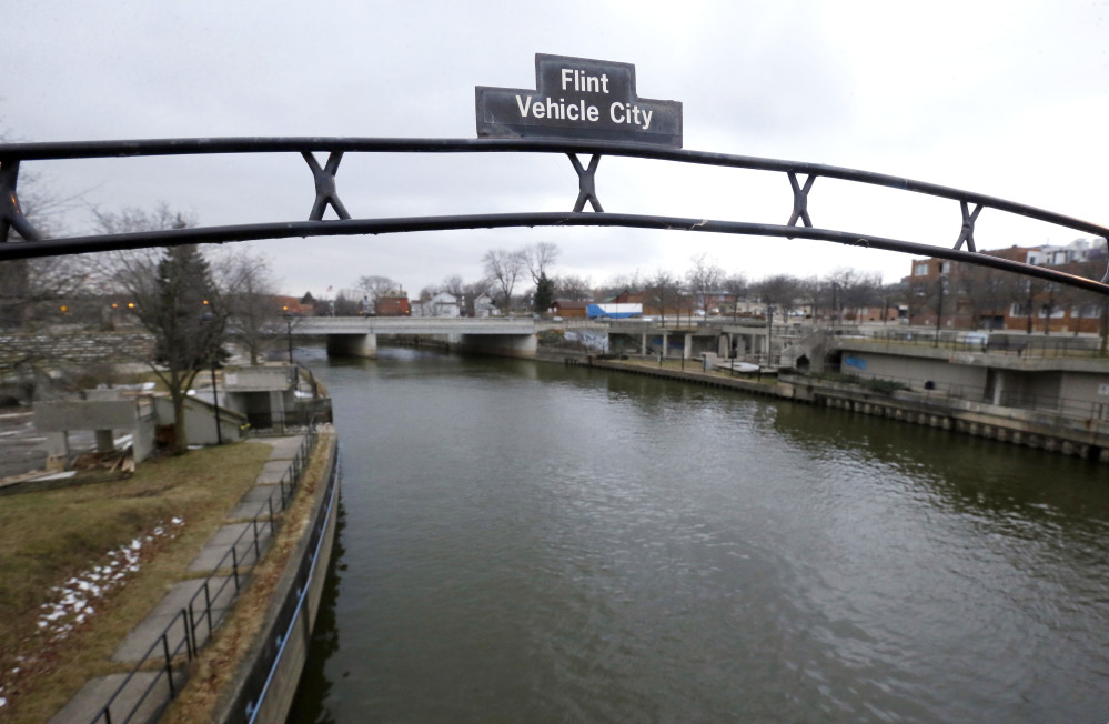 FILE - This Jan. 26, 2016 file photo shows a sign over the Flint River noting Flint, Mich., as Vehicle City. When Michigan Gov. Rick Snyder disclosed a spike in Legionnaires' cases on Jan. 13, 2016, he said he had learned about it just a couple days earlier. Internal emails however show high-ranking officials in Snyder's administration were aware of a surge in Legionnaires' disease potentially linked to Flint's water long before the governor reported the increase to the public last month. (AP Photo/Carlos Osorio, File)