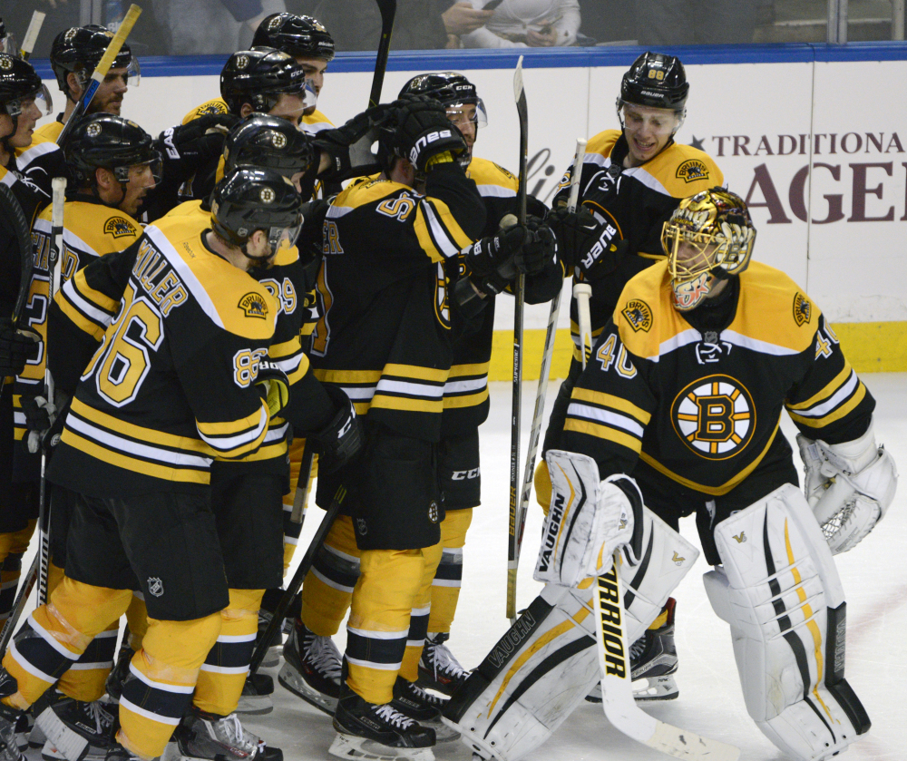 The Bruins surround goaltender Tuukka Rask after he stopped the final shot of the shootout to preserve a 3-2 win Thursday night in Buffalo.