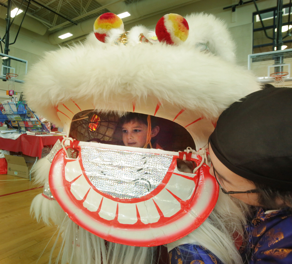 Rodger Wong helps Will Lindecamp, 3, try on a lion's head in the gymnasium at Westbrook Middle School during a Chinese New Year celebration sponsored by the Chinese and American Friendship Association of Maine and the Confucius Institute of the University of Southern Maine, on Saturday.