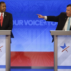 Republican presidential candidate Chris Christie points beyond Ben Carson to Marco Rubio (not shown), accusing the Florida senator of repeating a rehearsed 25-second speech during the Republican debate Saturday night.