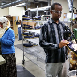 "In this Tuesday, Jan. 26, 2016 photo, Abdi Said, right, trims the rubber bottoms of Bean Boots at an L.L. Bean factory in Lewiston, Maine. Said, a refugee, was originally put in San Jose, California, before he moved cross-country to Lewiston. ""We are working hard and we're going to school and everything - like regular American people. They see that we are not different,"" he said."