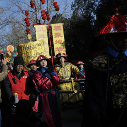 Qi Xue'en, a performer dressed as a Qing Dynasty emperor, seated on a sedan chair, center, is carried during the ancient Qing Dynasty ceremony in which emperors prayed for good harvest and fortune at a temple fair in Ditan Park during the first day of the Chinese Lunar New Year in Beijing, Monday.