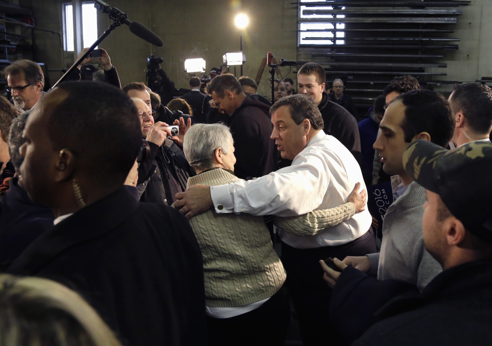 Republican presidential candidate, New Jersey Gov. Chris Christie greets a potential voter after a town hall-style campaign event, Monday in Hudson, N.H.