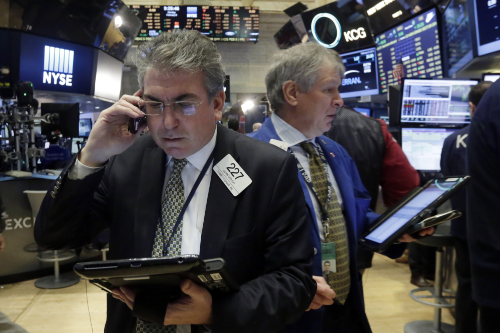 Traders John Bishop, left, and Richard Newman work on the floor of the New York Stock Exchange, Monday.