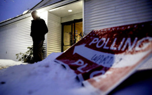 A voter leaves a polling site at dawn after casting a ballot in the New Hampshire primary Tuesday in Nashua.