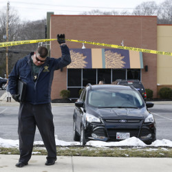 An investigator walks beneath police tape at the scene of a shooting at a shopping center in Abingdon, Md., on Wednesday.