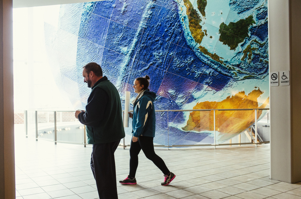 Nicole Cary holds a map of Allagash while walking with Walter Cary inside the lobby of the DeLorme Map Store in Yarmouth. The map store is not part of the Garmin deal, so those employees are expected to lose their jobs.